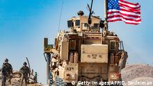 A US soldier sits atop an armoured vehicle during a demonstration by Syrian Kurds against Turkish threats at a US-led international coalition base on the outskirts of Ras al-Ain town in Syria's Hasakeh province near the Turkish border on October 6, 2019. - Ankara had reiterated on October 5 an oft-repeated threat to launch an air and ground operation in Syria against a Kurdish militia it deems a terrorist group. (Photo by Delil SOULEIMAN / AFP) (Photo by DELIL SOULEIMAN/AFP via Getty Images)