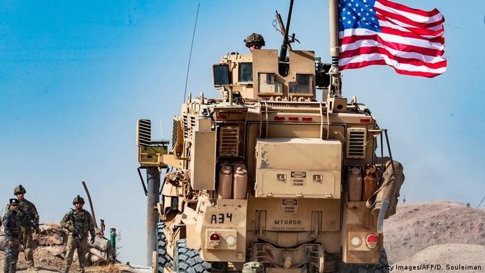A US military vehicle near the Turkish border, with Syrian Kurds next to it (Getty Images/AFP/D. Souleiman)