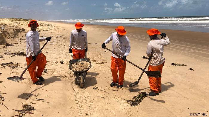 Homens limpam praia atingida por manchas de óleo em Sergipe