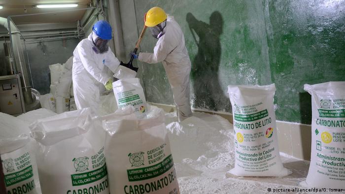 Arbeiter füllen in einer Pilotanlage am Salzsee von Uyuni in Bolivien Lithiumkarbonat in Säcke ein