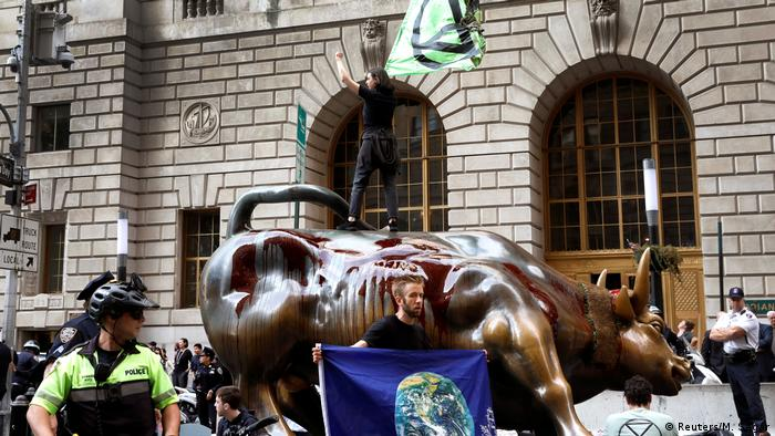 Protesters in New York douse the statue of the charging bull near Wall Street with blood