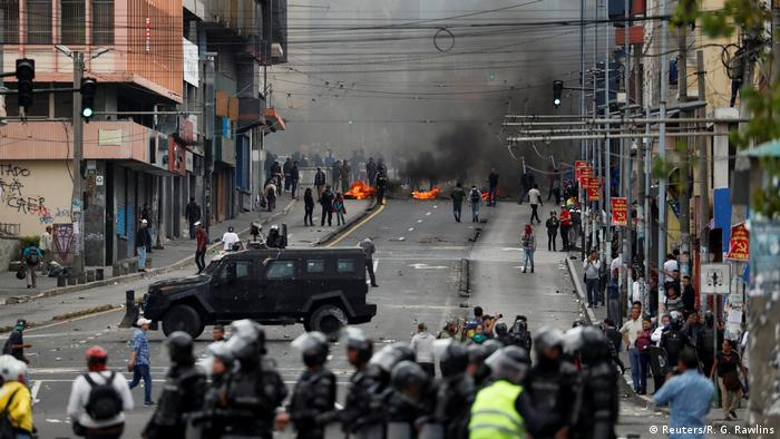 An armored 4x4 stands between protesters and police in Quito, Ecuador