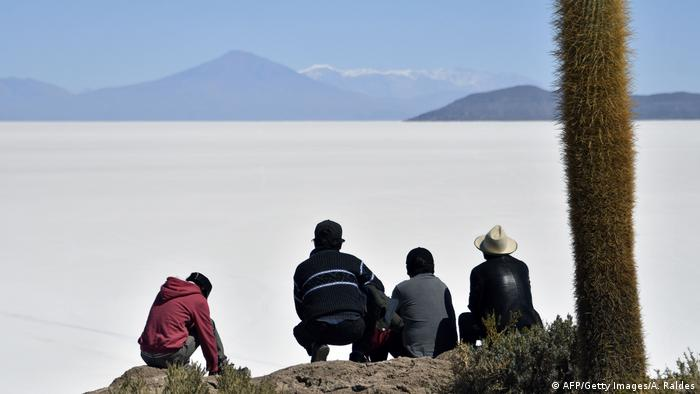 A group of men sit on the fringes of the Salar de Uyuni and looking over the salt flat