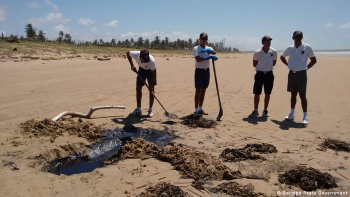 Four men dig up spilled oil on a beach in Sergipe (Sergipe State Government)