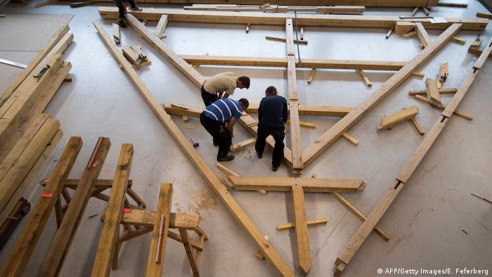 Carpenter apprentices work on a roof truss matching one of Notre Dame Cathedral's as part of their training