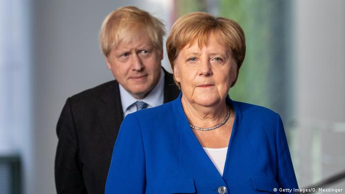 Premiê Boris Johnson anda atrás de Angela Merkel, com olhar preocupado