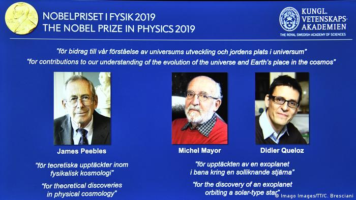 A screen displays the portraits of the laureates of the 2019 Nobel Prize in Physics (L-R): James Peebles, Michel Mayor and Didier Queloz
