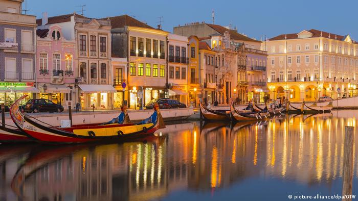 Gondolas on the main canal of Aveiro after sunset.