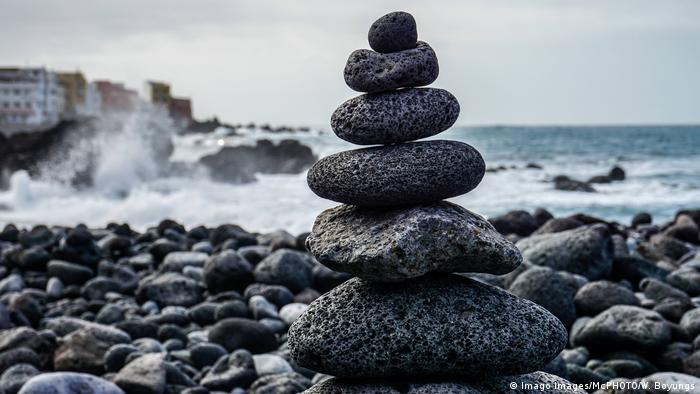 A small tower of five stones on a pebble beach