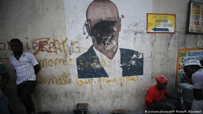 A man in front of a wall painted with a defaced picture of Haiti's president (picture-alliance/AP Photo/R. Blackwell)
