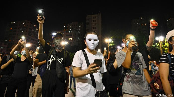People wear masks and light up their mobile phones during a flash mob rally