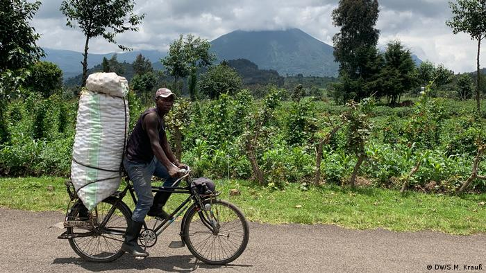 Man rides bicycle with Valcono mountain on the background (DW/S.M. Krauß)