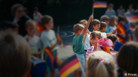 Children holding up German flags in blurry focus