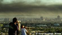 388200 02: Spectators on Signal Hill watch as toxic smoke blows over downtown Long Beach, CA, April 23, 2001, from a fire at the Tosco oil refinery in Carson, 15 miles south of Los Angeles. The refinery was running at full capacity, around 125,000 barrels of oil per day, when a blaze broke out in the ''coker'' unit, where petroleun coke is burned in the making of gasoline. Lost production could add to the recent spike in gasoline prices, which analysts say could hit $3 a gallon or more. (Photo by David McNew/Newsmakers)
