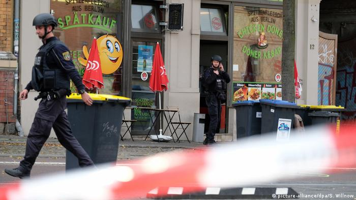 Police stand outside a kebab shop where a shooting took place in Halle, Germany