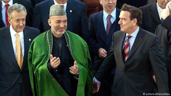 المستشار الألماني السابق غيرهارد شرويدر والمبعوث الأممي الأخضر الإبراهيمي والرئيس الأفغاني السابق حامد كرازي في مؤتمر بون