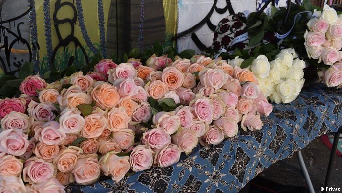 دویست شاخه گل، با روبانهای حاوی مشخصات زندانیان، هدیهای به بازدید کنندگان و گردشگران کوچه کلاریون. عکاس تصاویر گالری: مهرگان پزشکی.