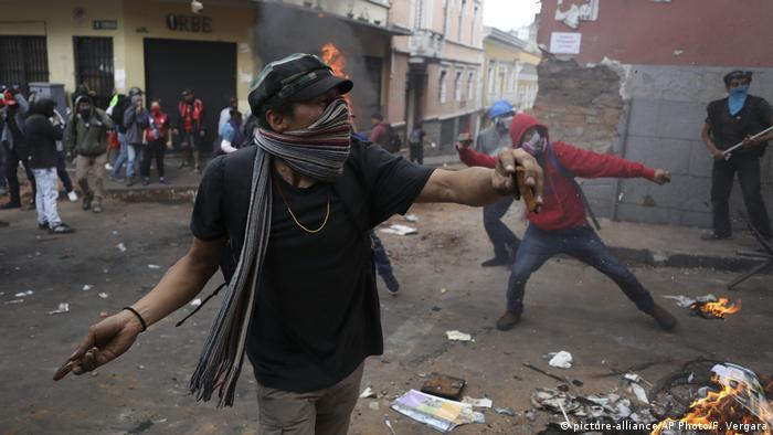 An anti-government demonstrator hurls rocks at police in Quito, Ecuador