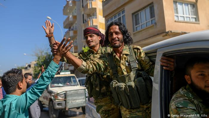Syrian opposition fighters enter Tel Abyad on a truck and wave to a passer-by.