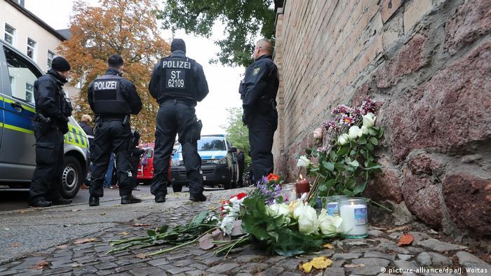 Flore se velas depositadas em muro sinagoga, com policiais em segundo plano