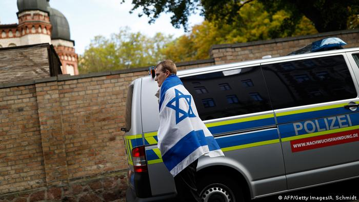 man wearing Israel's flag is seen on October 10, 2019 at the synagogue in Halle