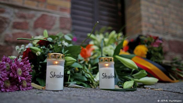 Blumen und Kerzen liegen vor der Synagoge in Halle.