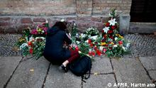10.10.2019 *** A woman places flowers at a makeshift memorial in front of the synagogue in Halle, eastern Germany, on October 10, 2019, one day after the attack where two people were shot dead. - German leaders visited the scene of the deadly anti-Semitic gun attack carried out on the holy day of Yom Kippur, as Jews demanded action to protect the community from the rising threat of neo-Nazi violence. (Photo by Ronny Hartmann / AFP)
