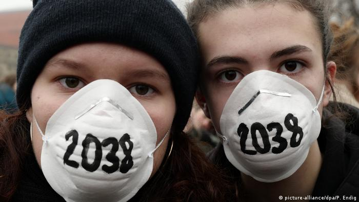German environment protesters wear face masks with the date 2038 written on them