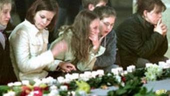 Unidentified people grief over the victims of a school shooting in the Cathedral of Erfurt, eastern Germany, Saturday, April 27, 2002, the day after a former student killed 16 people before he killed himself in the Gutenberg high school. (AP Photo/Michael Probst)