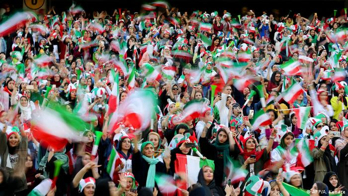 Iranian women watch a football match in a stadium (AFP/A. Kenare)