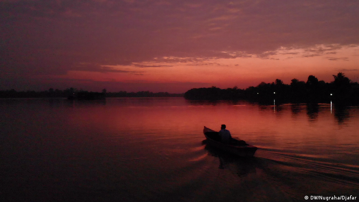 Nelayan Rukam, Alfian, 47 tahun, mengendalikan perahunya menyusuri sungai Batang Hari, Jambi, untuk mencari ikan.