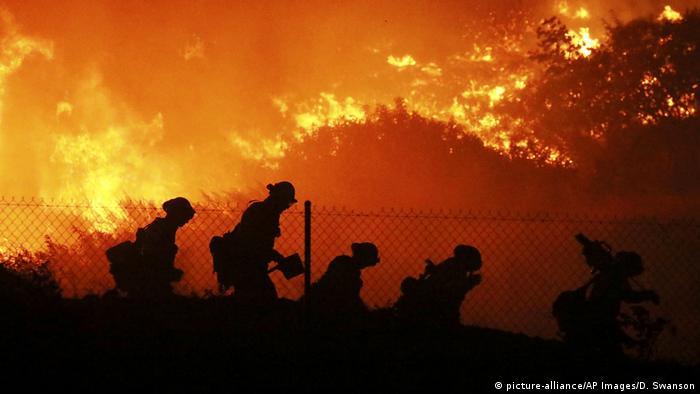 Four people walk a long the line of a fence with a raging fire in the background