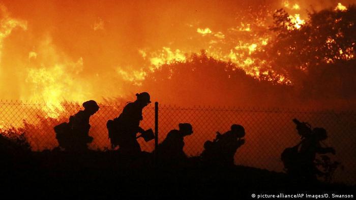 Vier Menschen laufen entlang eines Zauns. Hinter ihnen brennt ein großes Feuer