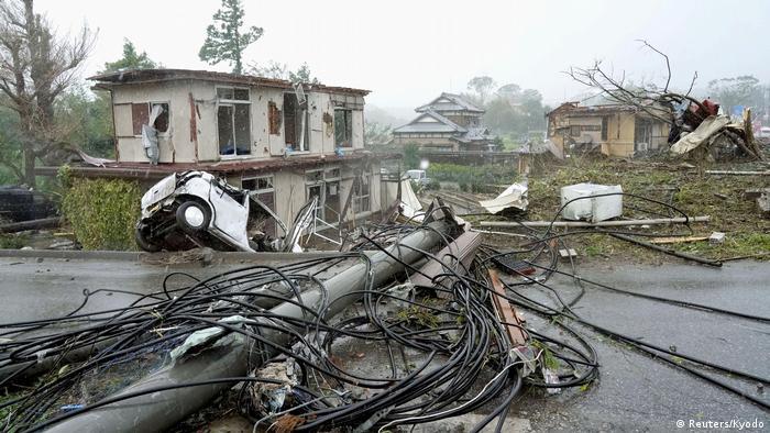Последствия тайфуна Хагибис в городе Итихара: разрушенный дом и автомобиль, поваленный столб