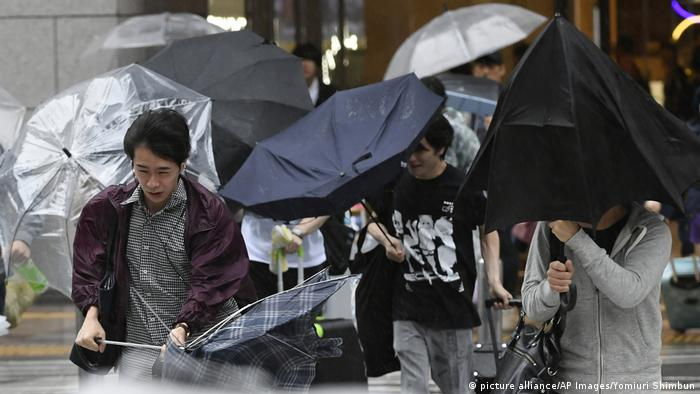 People hold their umbrellas tight as a strong wind blows in Osaka
