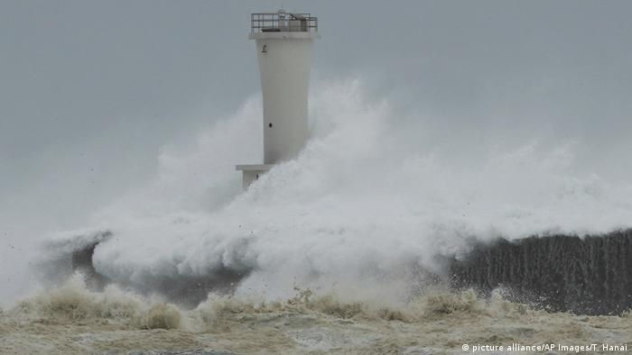 Storm waves hit a breakwater and lighthouse in the town of Kiho
