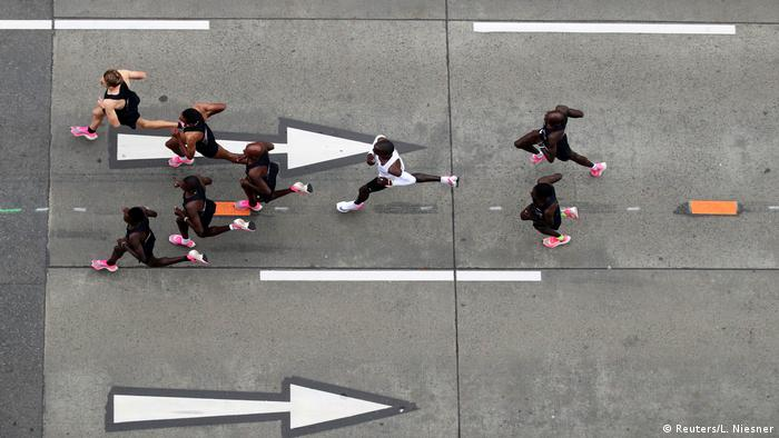 Eliud Kipchoge runs in between his pacemakers (Reuters/L. Niesner)