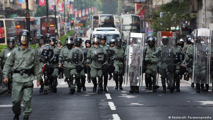 Hong Kong police march along the streets of Hong Kong holding riot shields and dressed in green.