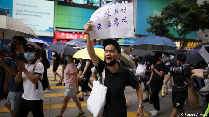 A Hong Kong protester holds up a sign against emergency laws in Hong Kong