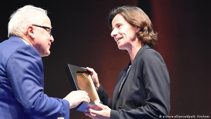 DFB president Fritz Keller presents Bettina Wiegmann with a trophy at the Hall of Fame