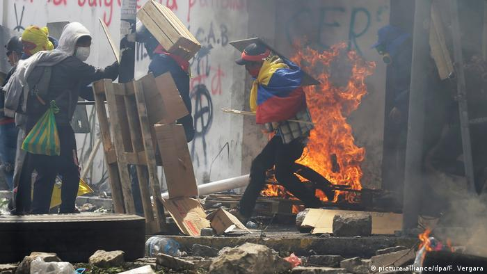 Protesters in Quito with burning wooden pallets in background