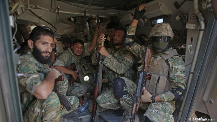 Turkish-backed Syrian fighters sit inside an armored personnel
