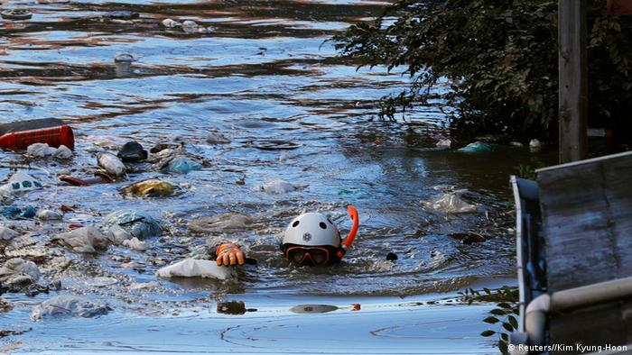 A rescue worker wearing a helmet and snorkel swims through a flooded residential area