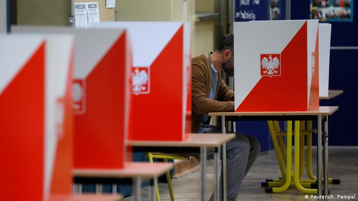 A man at a voting booth during the parliamentary election in Warsaw, Poland