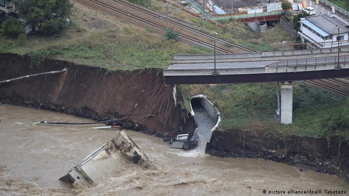 An aerial photo shows a bridge and road collapsed due to the Chikuma River overflowing