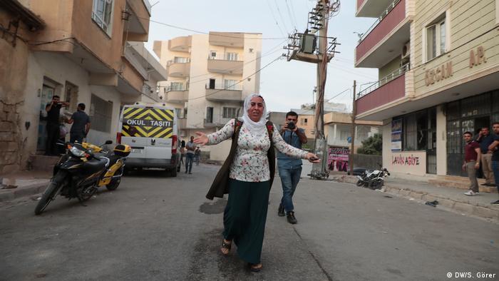 Mulher de véu corre de braços abertos em rua da Síria