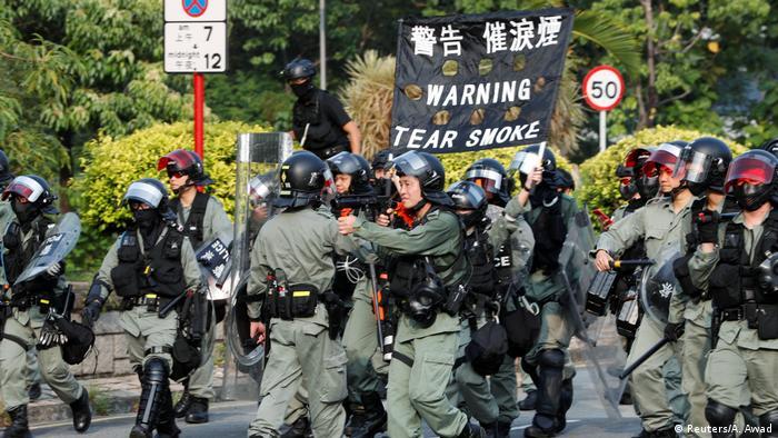 Hong Kong police carry sign saying 'Warning, tear smoke'