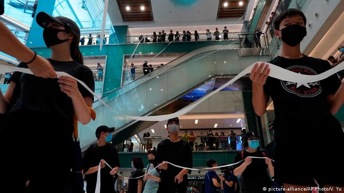 Hong Kong protesters wear masks in a shopping mall and form a ribbon chain