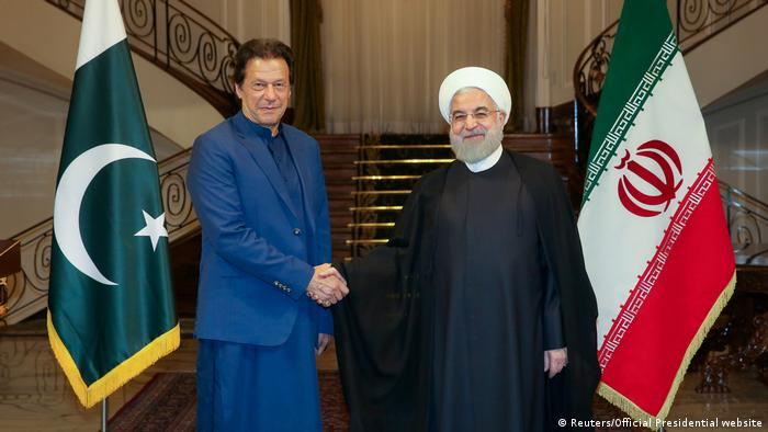 Iranian President Hassan Rouhani shakes hands with Pakistani Prime Minister Imran Khan in Tehran, Iran, on October 13, 2019
