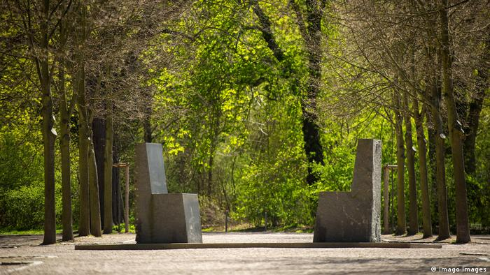 Stone slabs resembling chairs face each other in a forested setting